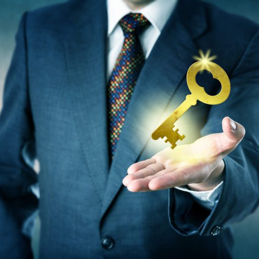 Business man is offering a golden key in his open palm. Business concept for key to success access to knowledge secure contract turnkey solution corporate secrets safe investment and leadership.